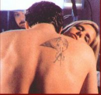 Another shot of Angel's back, this time probably from the scene in 'Graduation Day' when Angel feeds from Buffy. A man, presumably a crew member, seems to be watching in the background. The tattoo is slightly clearer although its exact nature is still unapparent. It is noticably higher up his back than in the first picture.