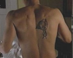 A rather dark screen capture from 'Angel' showing Angel with his shirt off after being injured by 'The Three'. The tattoo is visible as a winged creature above the letter A.